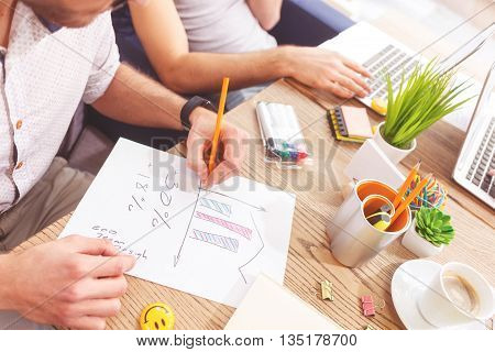 Close up of creative team planning new project. Man is sitting at table and writing with concentration. His colleague is using a notebook