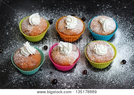 Muffins in colorful silicone forms with whipped cream