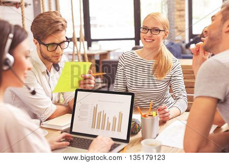 Joyful creative team is discussing a project with aspiration. They are sitting at desk and smiling. Blond woman is looking at camera with happiness. Her colleague is typing on laptop with headset