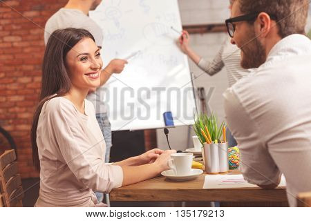 Happy man and woman are talking and smiling. They are sitting at table and looking at each other with happiness. Their colleagues are standing and discussing project near board