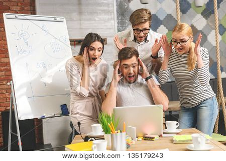 Creative team is looking at laptop with shock. They are opening mouth and raising arms to head