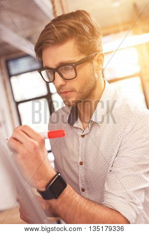 Handsome young man is writing his ideas on board with inspiration. He is standing and holding a highlighter