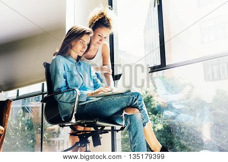 Hipsters Girls using Laptop modern Loft Studio.Students Researching Process.Young Business Team Working Creative Startup modern Office.Analyze market stocks, new strategy.Blurred, film effect.Horizontal