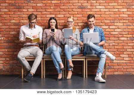 Cheerful students are having fun with laptop, tablet and mobile phone. They are sitting on chairs and smiling. Only one man is studying with concentration