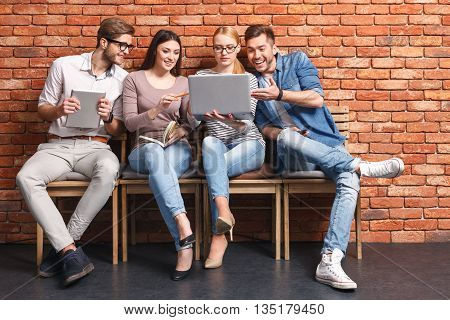 Joyful four young people looking at the laptop and smiling. Man is sitting on chair and holding tablet. Woman is carrying a notebook