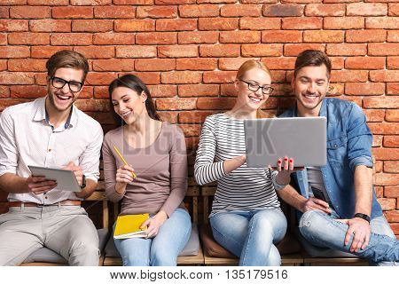 Happy young friends are sitting on chairs in row and laughing. Man and woman are looking at laptop. Guy and girl using tablet with interest