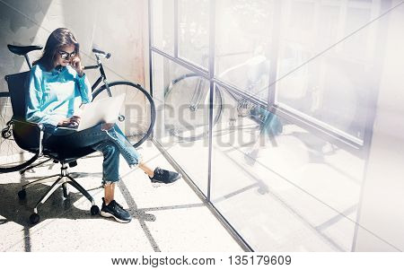 Hipster Girl using Laptop modern and sunny Loft Studio.Student Researching Process Work Time.Young Business Woman Working Creative Startup.Panoramic windows background.Blurred, film effect.Horizontal