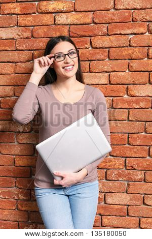 Clever young woman is carrying a laptop and smiling. She is standing near a wall and adjusting her eyeglasses