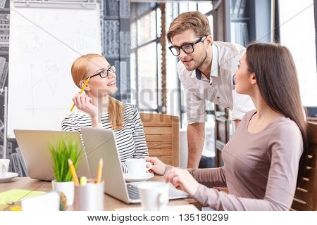 Cheerful creative team is talking with inspiration. Men is standing and looking at laptop with interest. Women are sitting and smiling