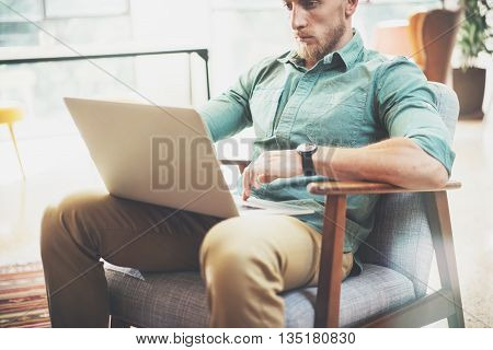 Bearded Businessman working Laptop modern Interior Design Loft Studio.Man relaxing Vintage chair.Use contemporary Notebook, blurred background.Creative Process New Startup Ideas.Horizontal, film effect