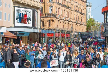 LONDON, UK - OCTOBER 4, 2015: Lots of people, tourists and Londoners walking via Leicester square, the famous destination of London for night life, cinemas, restaurants and bars