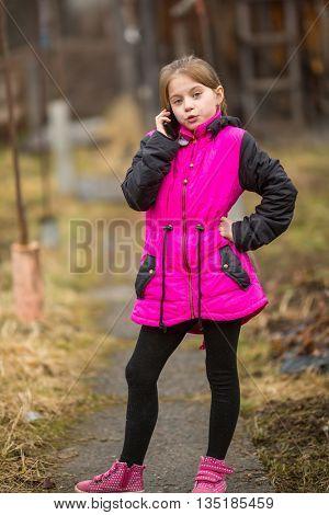 Little girl talking on mobile outdoors.