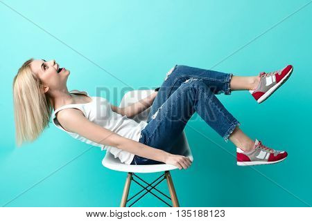 Cheerful blond girl is sitting on chair and relaxing. She is looking up with joy and laughing. Isolated on blue background