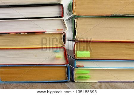 Textbooks with color bookmarks stacked on the wooden table