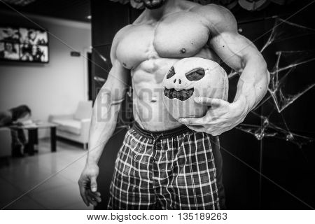 gym halloween theme gym halloween gourd bodybuilder in checkered shorts holds a pumpkin  in left hand, strong man with halloween pumpkin in his hand, black and white photo of sportsman's trunk