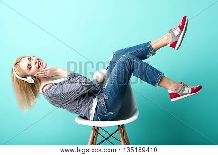 Pretty blond girl is listening to music from headphones and relaxing. She is sitting on chair and laughing. The lady is looking at camera with happiness. Isolated on blue background