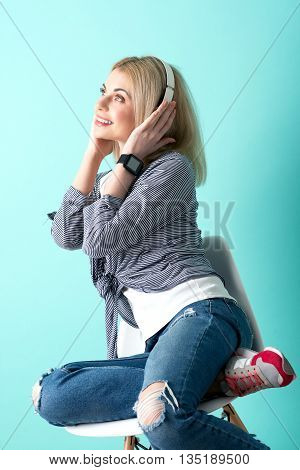 Beautiful young woman is enjoying music and dreaming. She is touching headphones and smiling. The lady is sitting on chair and relaxing. Isolated on blue background