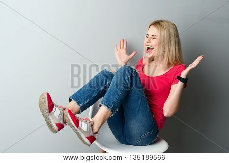 Attractive young woman is sitting on chair and laughing. She is gesturing with aspiration. Her eyes are closed with joy. Isolated on grey background