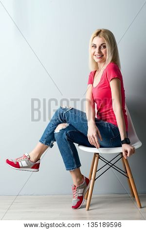 Pretty young woman is having a seat and relaxing. She is looking at camera with happiness and smiling. Her legs are crossed