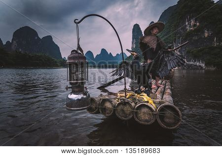 Guilin China - June 17 2014 : Shot of a cormorant fisherman standing on his bamboo raft with the cormorant bird flapping its wings at Li River Guilin China.