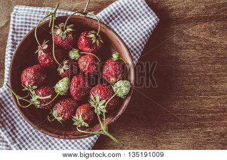 Fresh ripe organic strawberry on wooden background. Vintage rustic style and color tinting. Selective focus.