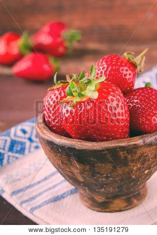 Ripe fresh juicy organic strawberries in old clay bowl on wooden background