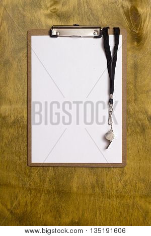 Whistle and paper for sports tactics on a wooden background