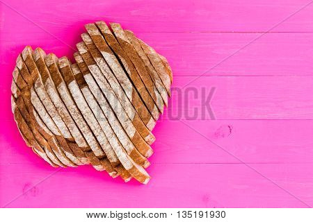 Heart Shaped Sliced Bread On Pink Background