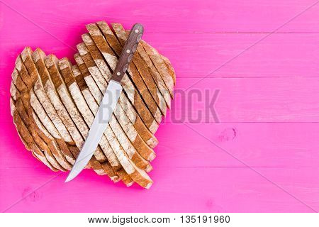 Heart Shaped Bread And Knife On Pink Background
