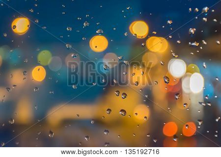 Rain drops and blurred bokeh night light background