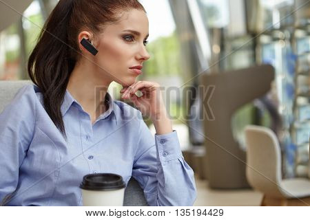 Businesswoman drinking coffee / tea in a coffee shop