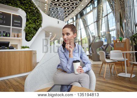 Businesswoman drinking coffee / tea in a coffee shop