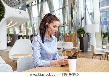 business woman with smile is sitting with touch pad in comfortable restaurant during recreation time, happy female student works on digital tablet and relaxes in coffee shop