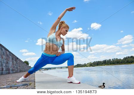 Woman stretching her leg by the river after running