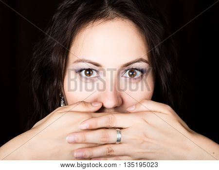 Close-up woman looks straight into the camera on a black background. She covered her mouth with her hand. expresses different emotions.