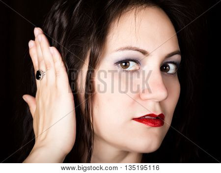 Close-up woman looks straight into the camera on a black background. laughing woman covers his ears with his hands. expresses different emotions.