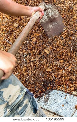 man worker using hoe equipment on the soil clay dirt