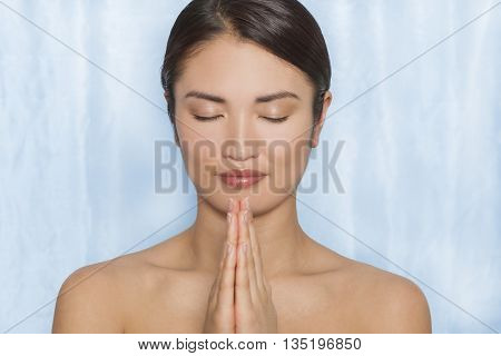 Studio shot of a beautiful young Japanese Asian woman or girl in a spa concept relaxed meditation