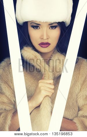 Beautiful Japanese Asian young woman or girl illuminated by glowing fluorescent tubes and wearing (fake) fur hat and coat