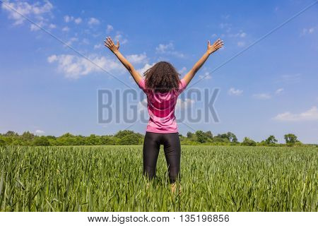 Rear view of young woman girl female runner jogger standing arms raised in celebration standing in green field with blue sky