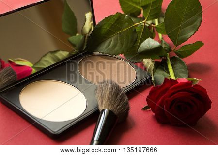 Dry textured correcting powder brush and rose on red textured surface. Makeup product to even out skin tone and complexion. Professional cosmetics. Rose reflecting in the mirror. Close-up image artistic retouching.