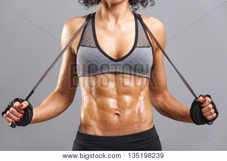 Fitness woman with jumping rope posing on grey background
