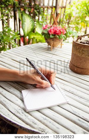 Female hand writing in a notebook on wooden table