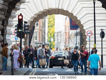 LONDON, UK - OCTOBER 4, 2015: Arch at Piccadilly street and lots of people crossing the road and walking pass