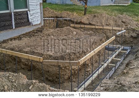 Ground has been dug out for footings for an addition. Forms have been built with plywood and rebar.