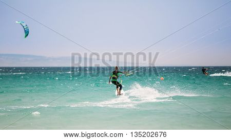 Tarifa, Spain - June 21, 2015: Kite surfing in Tarifa, Spain. Tarifa is most popular places in Spain for kitesurfing. Woman Kite surfer.