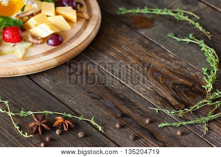 Frame on wood from cheese plate and herbs copy space. Top view on dark wooden background with wine snack catering platter and herbs, making frame with void.