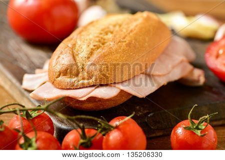 closeup of a braised turkey ham sandwich on a rustic wooden table next to some fresh tomatoes