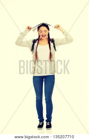 Teen girl with book over her head.