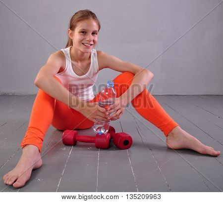Indoor portrait of young sportive teen girl with a bottle of drinking water while relaxing a in gym